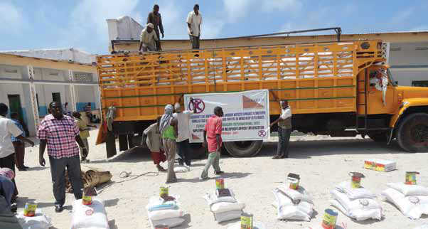 Emergency food aid provided by Human Concern International being unloaded at a distribution centre in Somalia.  Photo Credit: Human Concern International
