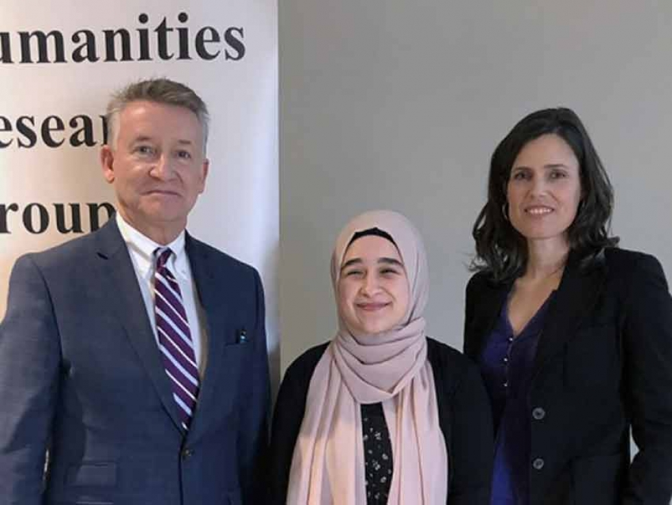 """Why Humanities?"" competition winner Rima Asfour (centre) accepts congratulations from UWindsor interim president Douglas Kneale and Humanities Research Group director Kim Nelson."