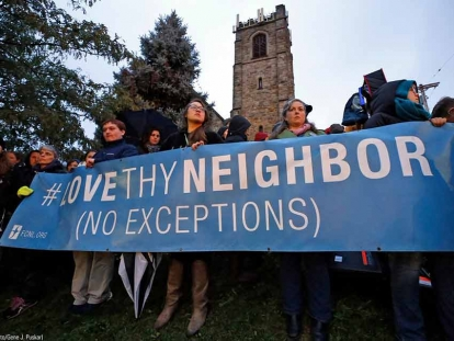 Mourners hold up a sign near the Tree of Life Synagogue in Pittsburgh where a gunman opened fire Saturday, killing 11 people and injuring six others