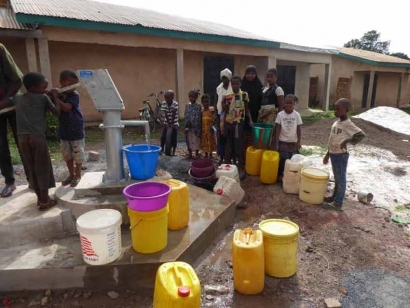 The photo was taken on October 10, 2020 at the well in Labé dedicated to Mamadou Barry. It is a typical family coming to get their provisions from the well.