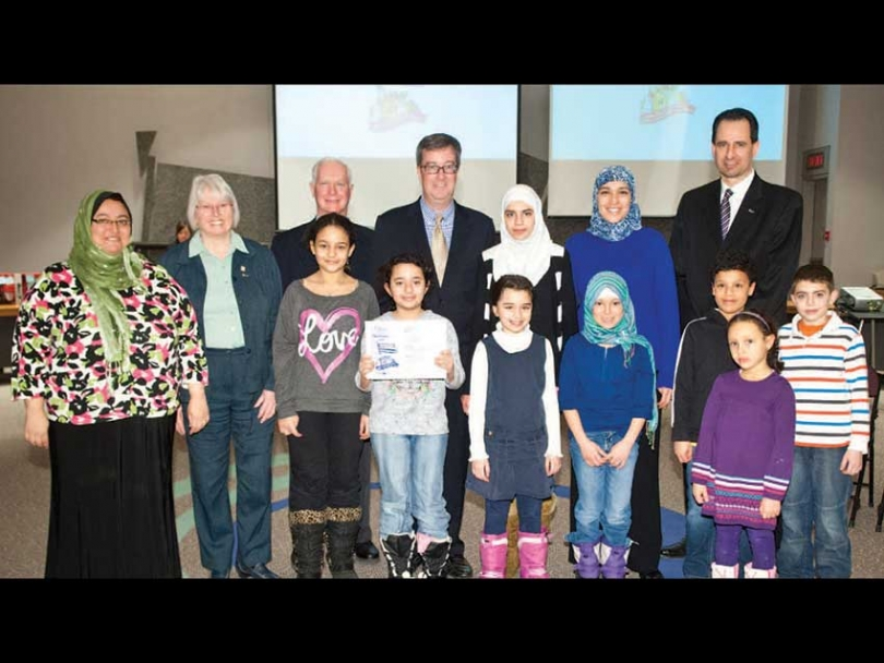 "Kanata Muslim Women and Children Adopt a Park and Receive Recognition. For several years, a group of Muslim women and kids in Kanata have participated in the annual ""Cleaning the Capital"" Campaign. On Feb. 6, they were recognized by the City of Ottawa. A sign at Morgan's Grant Park identifies the area as ""adopted"" by Kanata Muslims. (L-R, back row to front): Amany Zahran, Councillor Marianne Wilkinson, John Manconi, Mayor Jim Watson, Mariam Refaie, Nadine El-Hawary, Bill Houldsworth, Farah Osman, Huda Osman, Fatima Darwish, Noura Dawoud, Aly Matrawy, Ibraheem Refaie, Noor Matrawy."