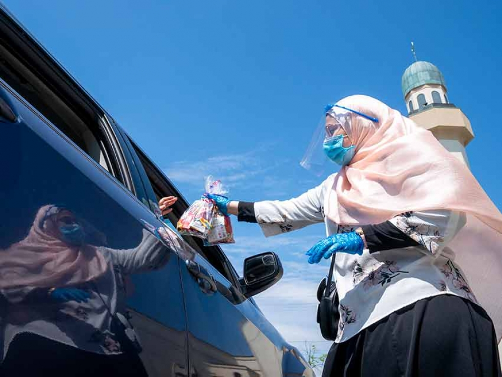 An Islamic Society of North America Mosque community member hands out candy to children in a drive-through Eid celebration in Mississauga, Ont., on May 24, 2020