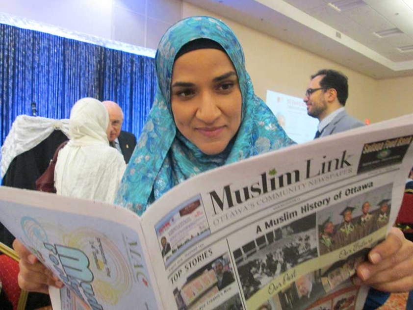 Dalia Mogahed reading a copy of Muslim Link at the National Council of Canadian Muslims fundraising dinner in Ottawa.