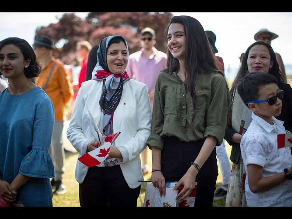 Maryam Sadat Montajabi, centre left, and her daughter Romina Khaksar, 15, who both moved to Canada from Iran in 2015, wait to have their photo taken with dignitaries after becoming Canadian citizens during a special Canada Day citizenship ceremony, in West Vancouver on July 1, 2019.
