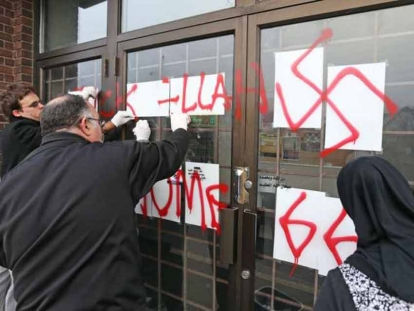 Hate graffiti on the Ottawa Mosque on Northwestern Ave being removed, November 18, 2016