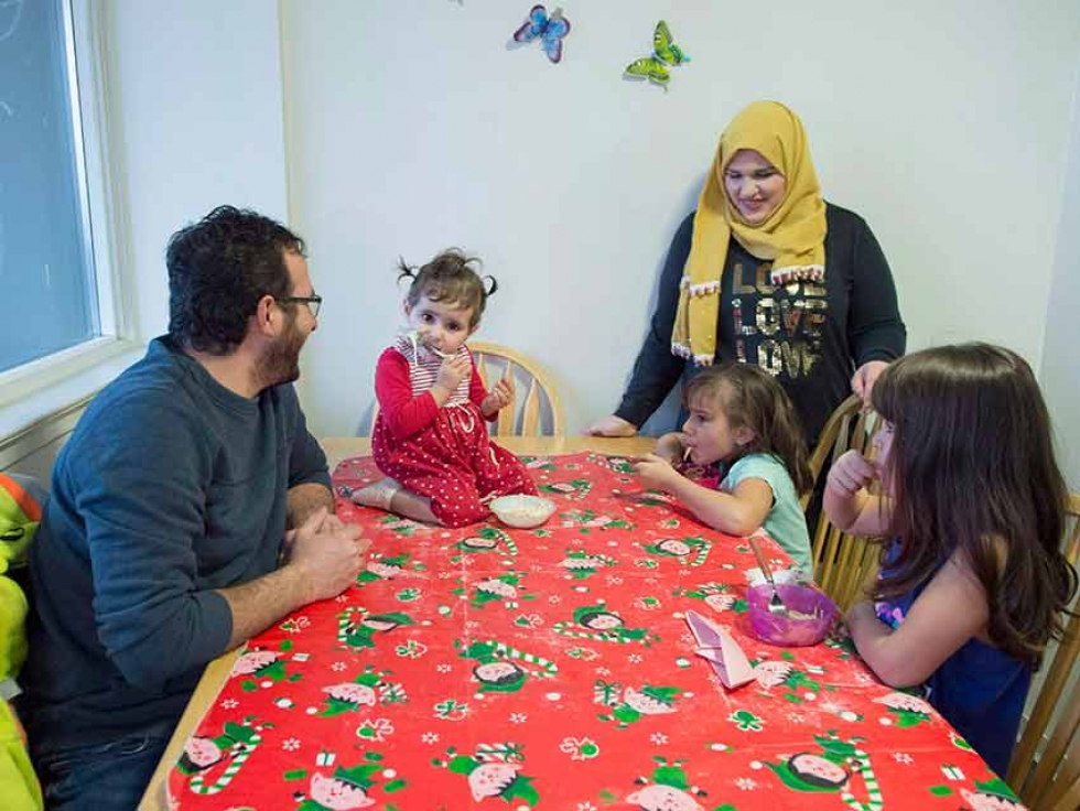 Syrian refugee family Mohammad Al Mnajer and wife Fouzia Al Hashish sit with their three daughters Judy, second left, Jaidaa, far right, and Baylasan as they eat their after school snack at their home in Mississauga, Ont., in December 2018.