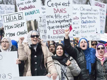 People hold up signs during a demonstration in Montreal in opposition to the Quebec government's newly tabled Bill 21.