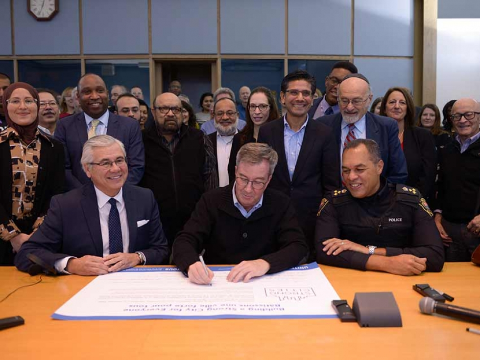 Mayor Jim Watson, Ottawa Police Chief Peter Sloly, and Michael Allen, CEO of United Way East Ontario sign on to United for All Coalition with community partners.