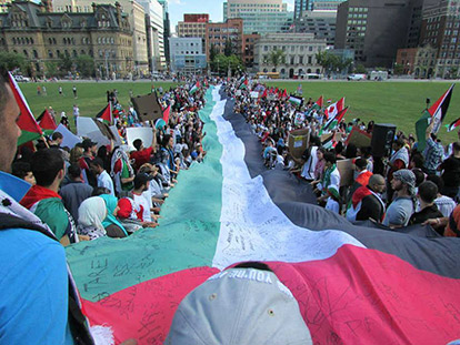 Demonstrators hold Palestinian flag at Parliament Hill