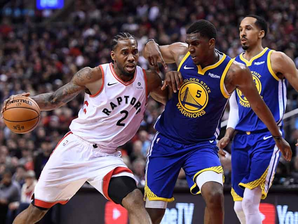 Toronto Raptors forward Kawhi Leonard drives up court as Golden State Warriors centre Kevon Looney defends during second half basketball action in Game 1 of the NBA Finals. THE CANADIAN PRESS/Frank Gunn