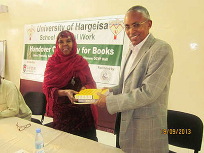 Asha Abdi Roobleh, President of Professional Social Workers Association is handing over books to the Honorable Minister of National Planning and Development Dr. Sa'ad Ali Shire. Dr Sa'ad is also the president of the Senate of the University of Hargeisa.
