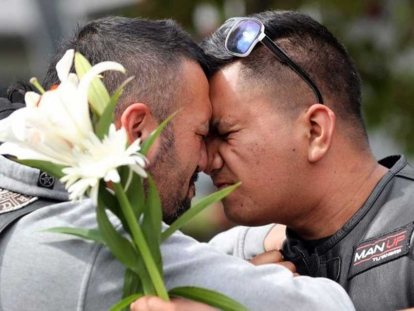 Mourners use the Maori traditional greeting or hongi at Hagley College on Saturday after the mosque attacks in Christchurch, New Zealand.