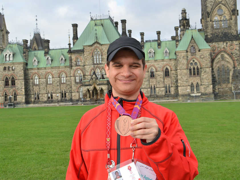 Bachar Awneh with his bronze medal in front of the Parliament Buildings.