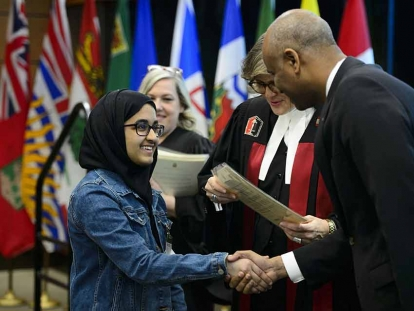 A youth receives her Certificate of Citizenship from Immigration Minister Ahmed Hussen and Citizenship Judge Marie Senecal-Tremblay on Parliament Hill in Ottawa on April 17, 2019