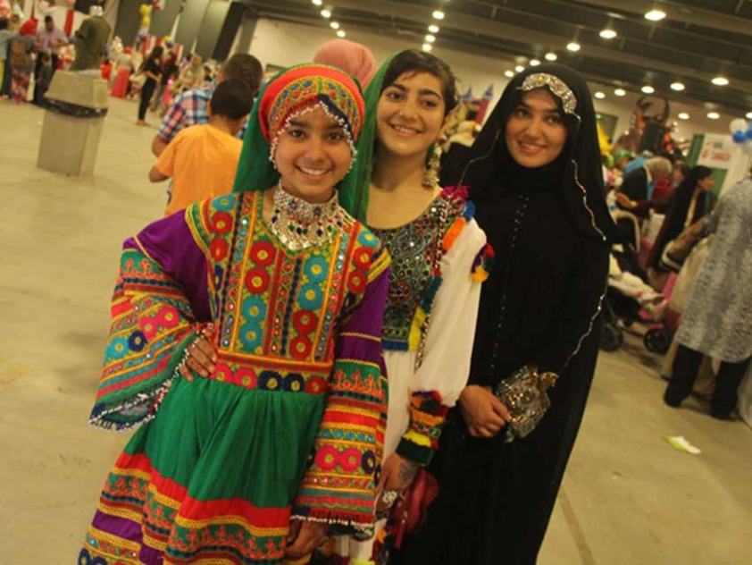 Girls wear traditional Afghan clothing at the MAC Eid and Summer Festival's Country Exhibition.