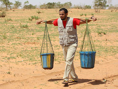 Zaid Al Rawni carries heavy buckets from the oasis to a village in Niger, mimicking the walk the people of the village have to carry out daily - the strain of the heavy weight visible on his face.