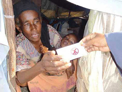 An internally displaced Somali woman and her children receive a ration card from Human Concern International for food aid.