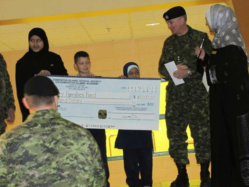 Students from the Edmonton Islamic Academy present a cheque to representatives from the Canadian Armed Forces.