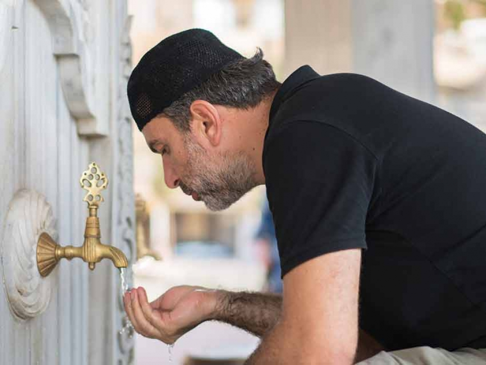 A Muslim man prepares for prayer by doing a ritual washing.