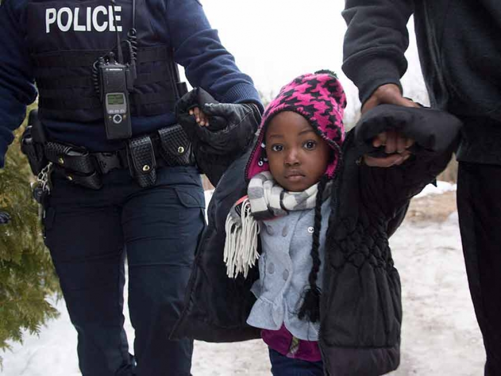 This 2017 photo shows a young asylum seeker being held by an RCMP officer and her father after crossing the border into Canada from the United States. THE CANADIAN PRESS/Paul Chiasson