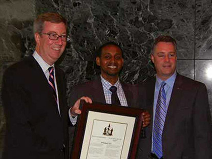 Mohamed Sofa (middle) holds his award and poses with Mayor Jim Watson (left) and Bay Ward Councillor Mark Taylor (right).