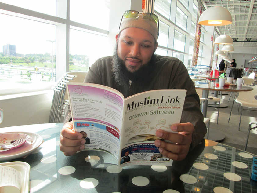 Pakistani Canadian imam reads Muslim Link's Business Pages during a meeting with the paper this month
