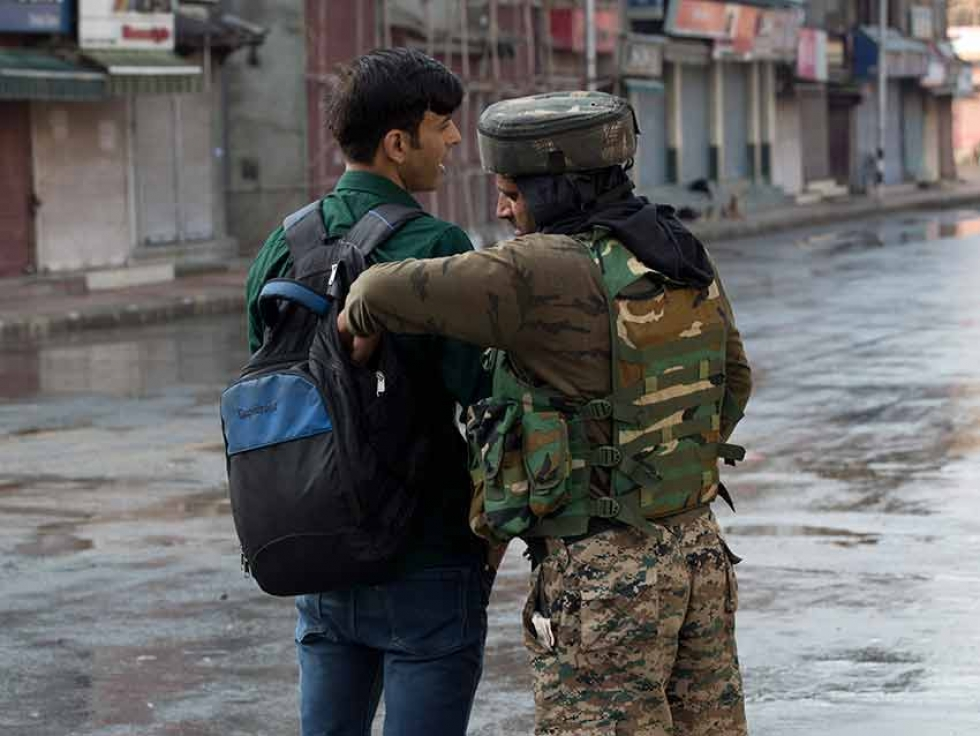 An Indian paramilitary soldier checks the bag of a Kashmiri man during curfew in Srinagar, Indian-controlled Kashmir.